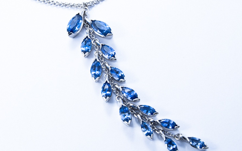 Floral platinum pendant with graduating marquise cut blue sapphires